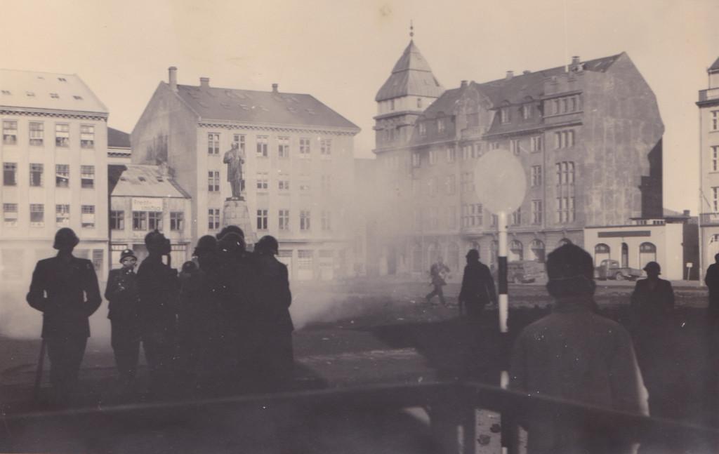 Lögreglumenn með gasgrímur standa við Austurvöll eftir slaginn.