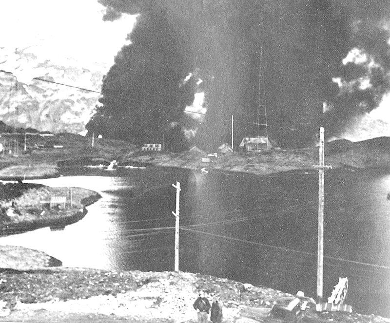 Dutch Harbor á Amaknak-eyju í ljósum logum eftir árás japanska flughersins.